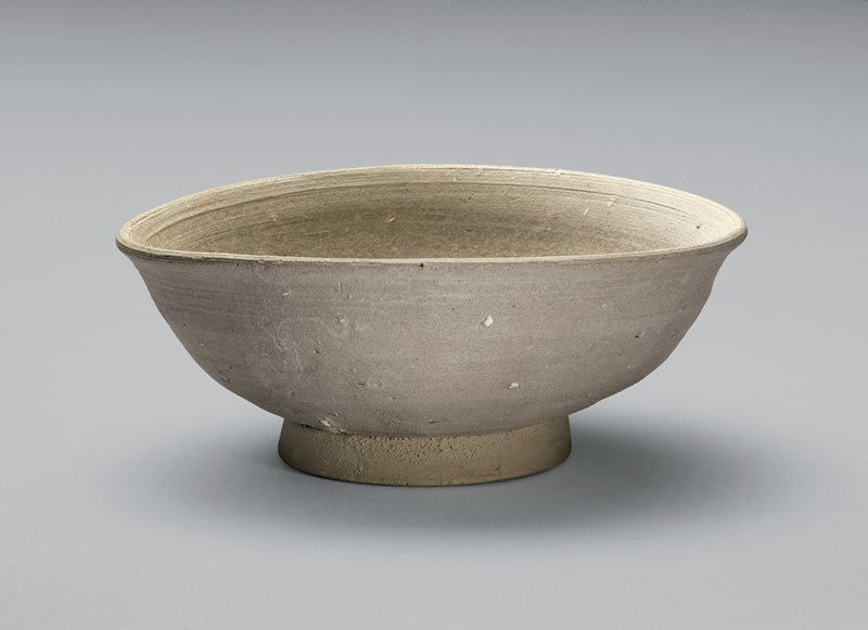 grayish-white stoneware bowl with slightly flaring lip; short foot; reddish-brown glaze in places around lip; streaks of white down outside; tiny pockmarks