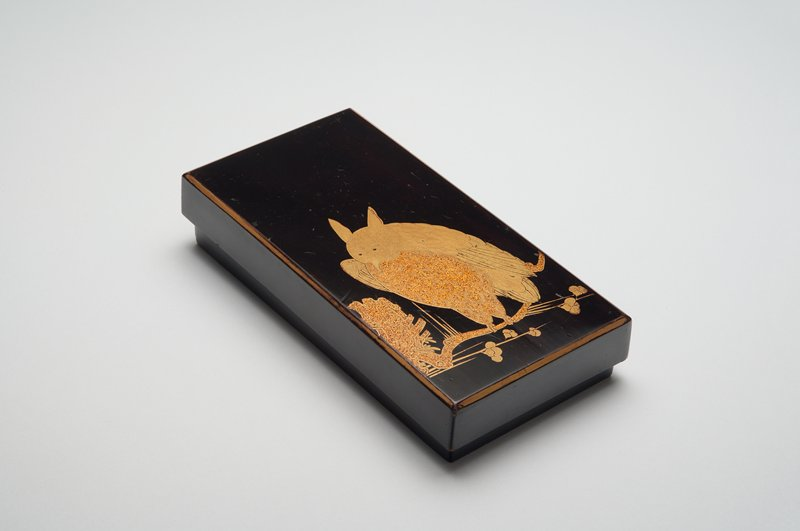 rectangular writing box in black lacquer; gold owl perched with wings slightly open on crooked blossoming branch; insert with ink stone and diamond-shaped water dripper with floral motif
