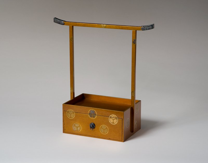 torii gate-shaped towel rack on small platform with deep drawer; each end of rail has an ornately decorated silver cap; gold and silver overlay of round crests with three hollyhock leaves