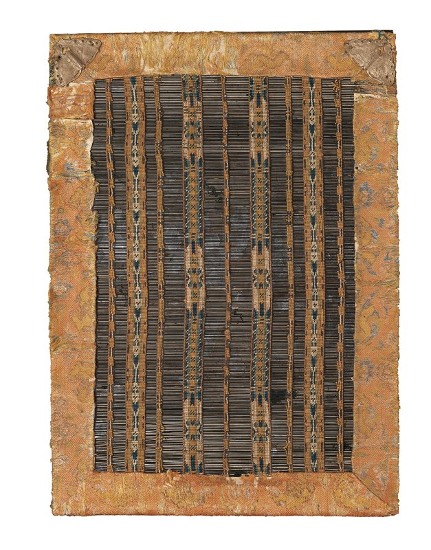 woven mat of thin black bamboo strips and colored floss; lined on back with green brocade; framed with orange and gold brocade; two butterfly-shaped metal fittings at bottom corners; separate small wooden tag