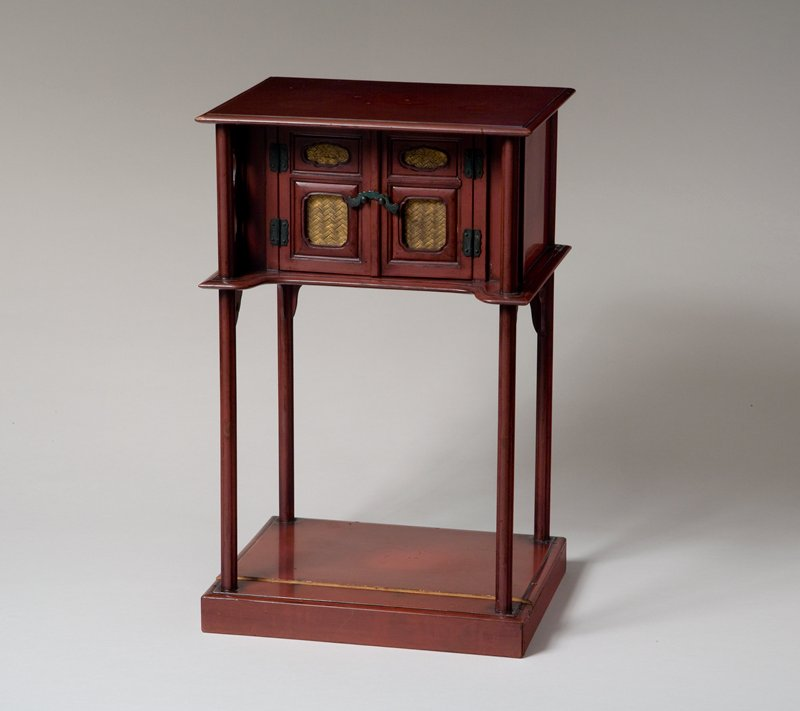 four posted red lacquered stand with enclosed area beneath top shelf; two doors in front with gold basketwork details; metal latch; carvings above legs