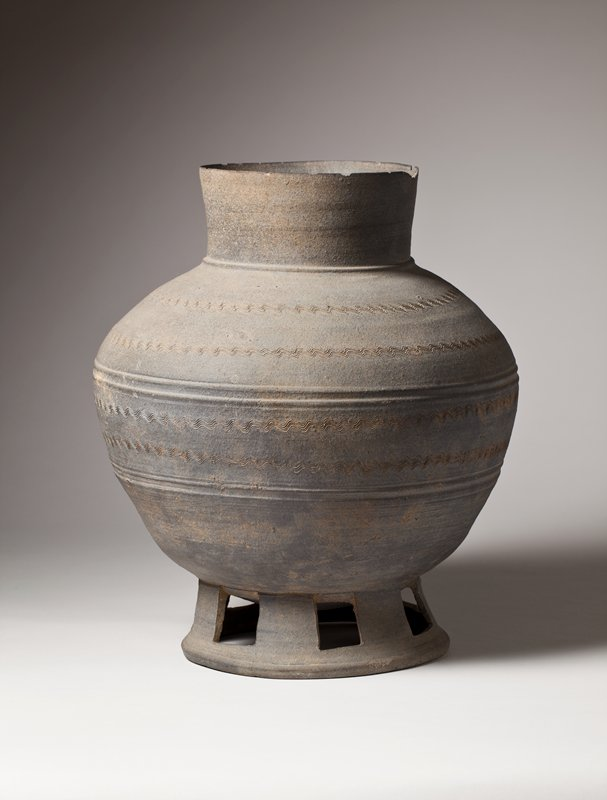 gray jar elevated on base with cut out squares; incised with horizontal bands of wavy lines and four concentric lines; tall neck with wide mouth