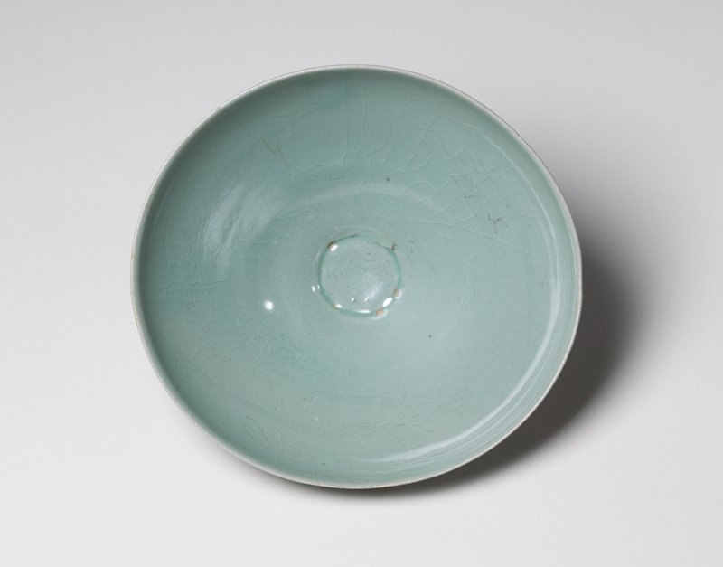 bowl with shallow, thinly incised birds flying inside with long, trailing feathers; very narrow base and wide mouth; celadon glaze