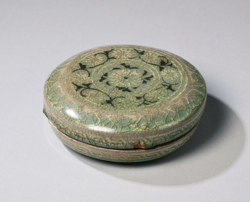 small, light gray-blue lidded container with inlaid design of stylized chrysanthemums and dark, arabesque stems; organic design around outer border