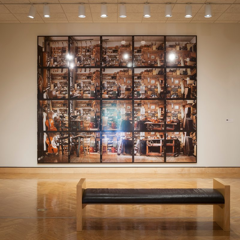 20 separate images/panels; view of a workspace in a repair shop for stringed instruments, crammed with tools, materials and stringed musical instruments; unglazed; mounted in five units of four vertical images (a,f,k,p - b,g,l,q - c,h,m,r - d,i,n,s - e,j,o,t); letters assigned from left to right in rows