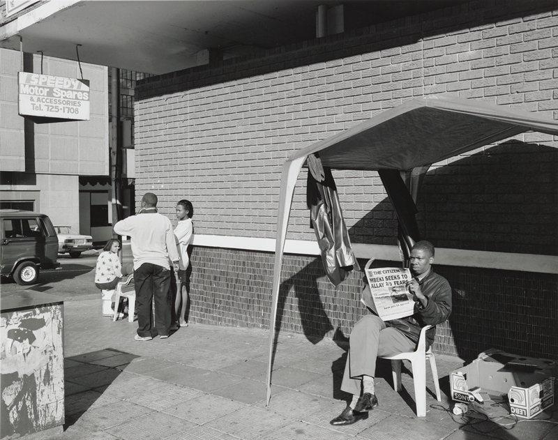 black and white photograph of a man sitting in a chair with an open newspaper under a canopy against a building at right; a group of three people on the left side, standing and seated by brick building wall