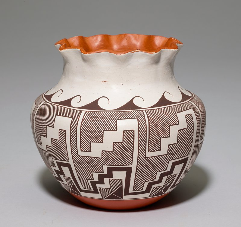 wide shoulder with vertical neck and scalloped rim painted terra cotta; white ground with dark brown step pattern below waves along shoulder