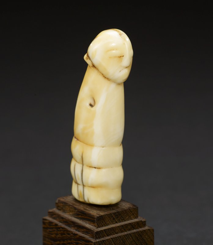 """cylindrical, curved knife handle with a round top that has faint facial features--eyes, nose, and mouth carved into it; a small rectangular shape protrudes at the back of the """"neck;"""" the bottom of the handle has three carved bands; the entire piece is light yellow in color--the natural hue of the ivory from which it is carved"""