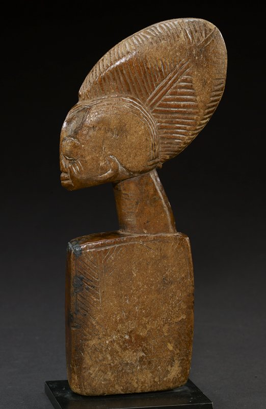 wood bust with round head covered with large, oval, patterned headdress protruding up and out; side of headdress are flat; face is carved in by small indentation--eyes, nose, mouth, and three small lines on each cheek; neck is long and thin and attached to a tall, square base with carvings on front; the piece overall is a light brown--natural hue of the wood