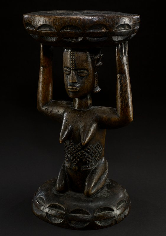stool with female caryatid; seat of the stool is round and flat, with the edges decorated with a repeating pattern of ovals; seat reset on the head and arms of the female figure, whose head is large and oval; eyes are large and oval, slitted down the middle; two rows of dots lead down to her nose, which is a large triangular shape; mouth is oval, with prominent lips; arms are thick and bent to support the seat of the stool; breasts are pointed and protrude out into space; beneath torso is carved in intricate patterns; figure is kneeling, resting on her bent legs which connect to the base of the stool; edges of the base are also carved in an oval pattern, similar to seat; entire piece is the natural color of the wood--a dark brown