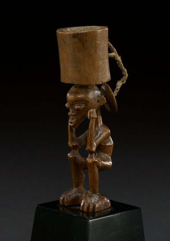 figure has a carved, hollow cylinder at the top of the head; behind the cup shape is a piece of cord with a thin circle of wood at the end, which forms a cover for the cylinder; figure's head is rounded, with prominent eyes; nose is small; lips are pursed into a point; ears are carved at the side of the head; neck is long and thin; figure is seated, with the arms bent at the elbows, with the hands resting on the face; back is hunched; knees are bent into a seated position; piece is anchored by the large feet which are connected at the heel; feet have notched carvings for toes; honey-colored