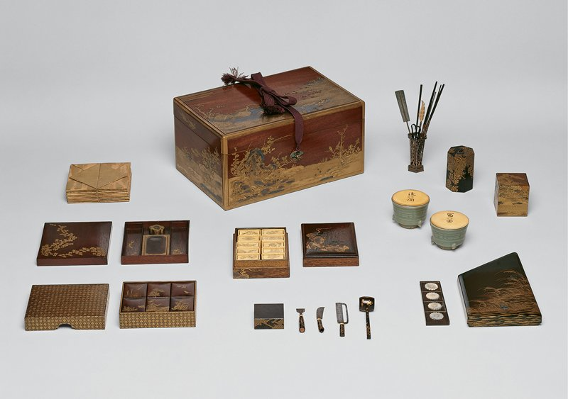 lacquer box of four parts; gold flecks in background; design of pine trees, maples, a harbor with rocks, boats; small buildings on stilts; blossoming trees, and rooftops