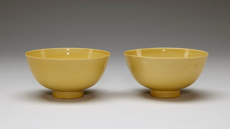 yellow glaze; rounded form with deep sides; vertical foot ring; white glaze with blue six-character inscription on underside; subtle incised designs with floral medallion surrounded by two rings at interior, alternating floral medallions and clouds on exterior with rings on foot and repeating floral petals around foot
