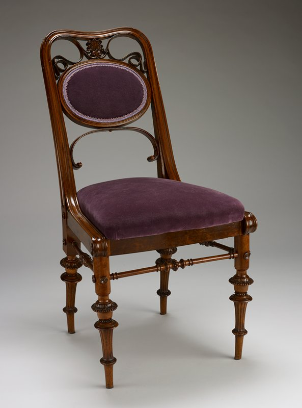 side chair with gently sloping back; oval purple velvet cushion at center of back; carved wooden ribbon detail on back with carved stylized Fleur-de-lies design at upper C; slightly curved carved, spindly legs; purple velvet seat that pops out