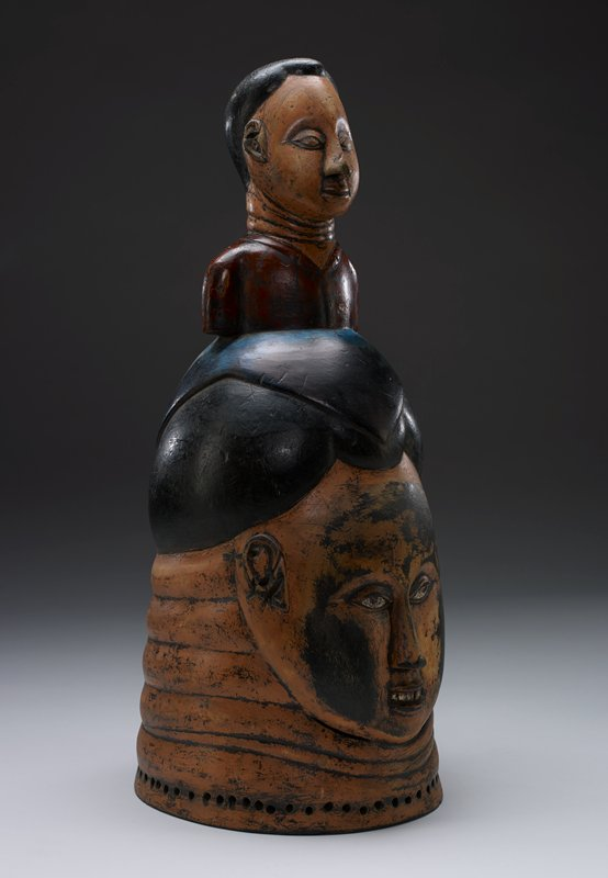 helmet mask; larger head at bottom with smiling face with teeth showing--gap between front teeth, long nose, full cheeks, almond-shaped eyes, small ears set high on head and forward toward face, with earlobes pierced; lower head has short black hair in a sort of cornrow/plaited style, delineated with incised zigzags, triangles and parallel lines; smaller head on top of lower head, with smiling face with teeth showing, almond-shaped eyes; high, forward-set ears with piercing in lobes and piercing at center back of PR ear; black hair of smaller head styled in three twisted ponytails--two on either side of head, one on back of head, with smooth parallel lines on hair on head; yellow and red fasteners at top of each ponytail; peach-colored skin