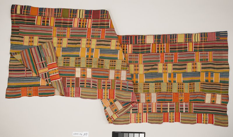 eighteen strips of fabric hand stitched together to form a panel; multi-colored fabric consisting of horizontal and vertical stripes; areas of woven thread alternate throughout overall design
