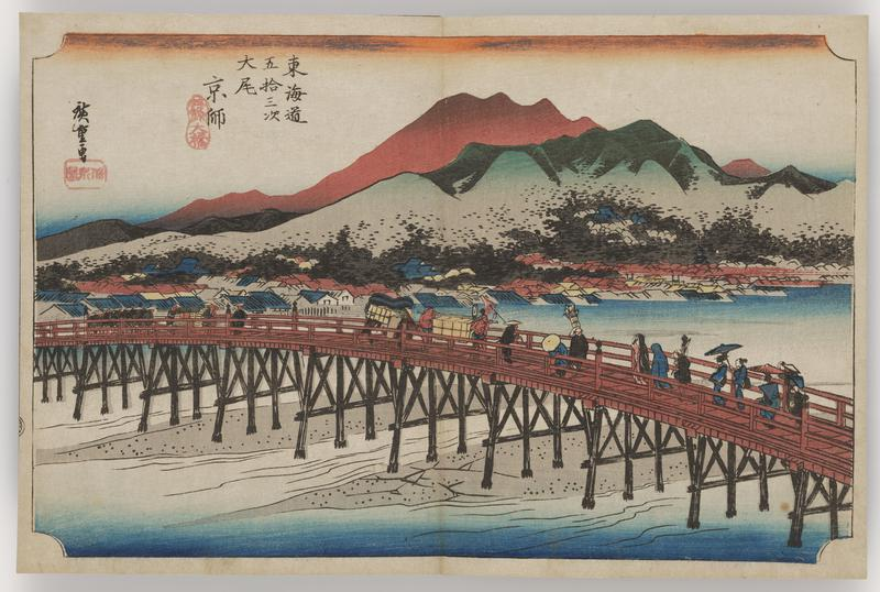 long, wide bridge crossing river; traveling procession with members carrying large parcels, boxes, and umbrellas cross the bridge; orange and green mountains loom at L; rooftops from the buildings of a large city on the shoreline to R of bridge