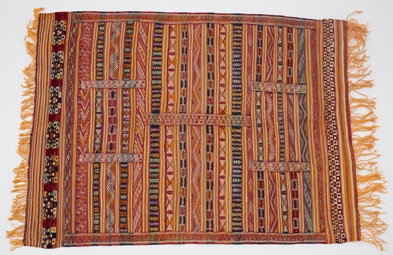 primarily light brown/rust--multicolors; horizontal patterned stripes (zigzags, diamonds, X's) with five vertical zigzag bands; checked pile bands with central squares at ends, with stripes and twisted orange fringe at short ends; heading band on back at one short end (top)
