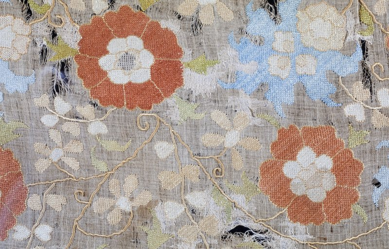 Panel, oblong, of fine linen material embroidered with leafy vine and blue and henna flowers. Linen.