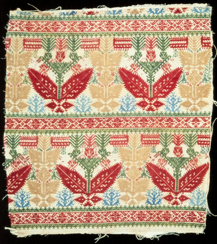 Linen embroidered in cross stitch with a conventionalized tree motive repeated in a formal design in all-over pattern. Red, green, blue and gold silks used.