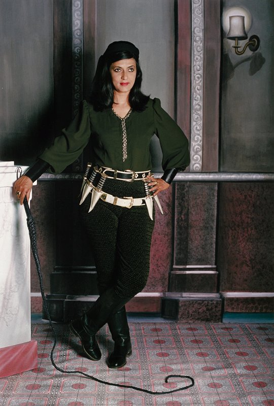 woman standing in powerful pose, holding a whip in PR hand and resting against a small column; white dagger belt around her waist; painted backdrop with marble panels and a light