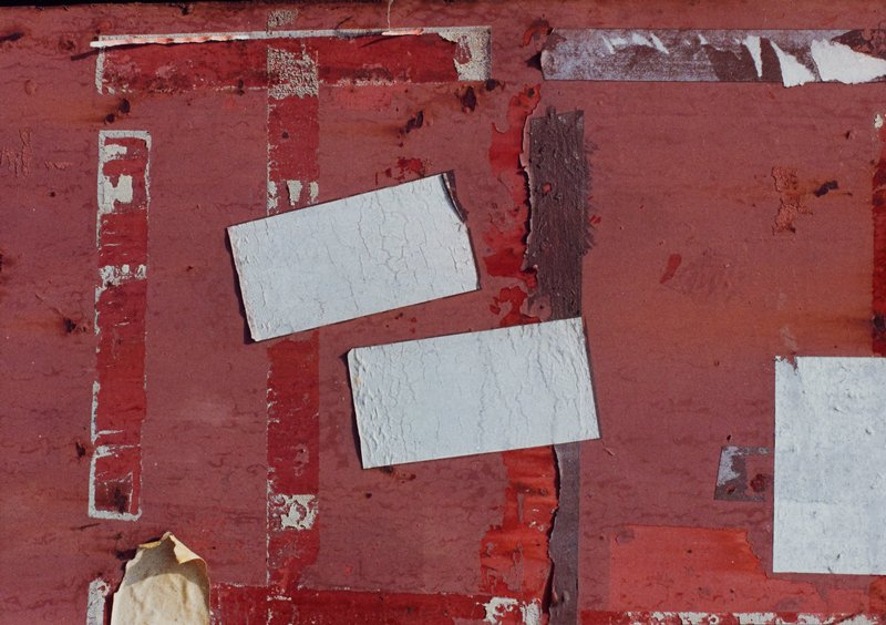 red background with patches of blistering, peeling paint; strips of tape residue; two patches of gray adhesive near C and another near UL