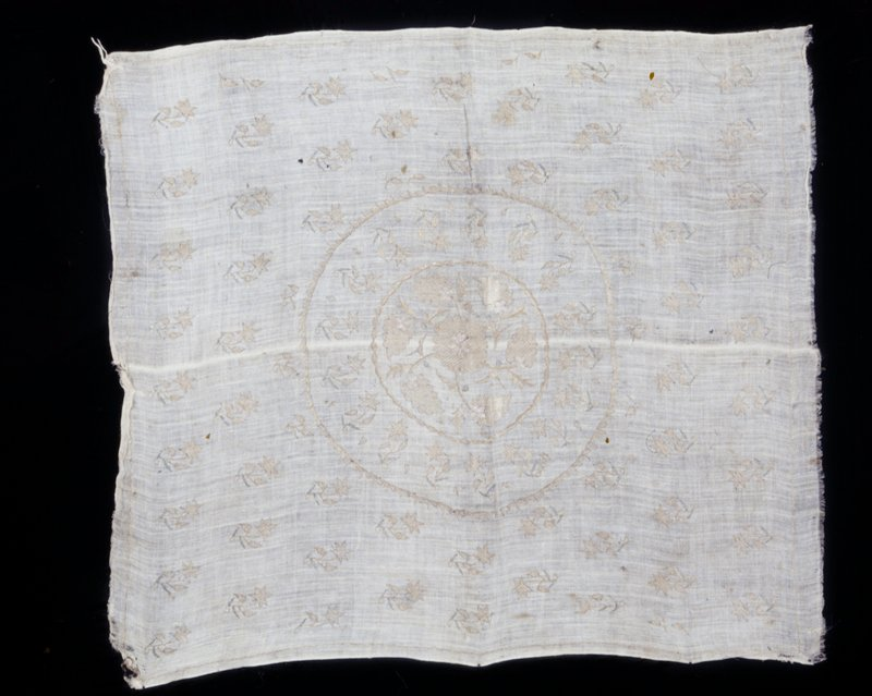 Cover, of loosely woven linen embroidered in tinsel thread with rows of small floral sprays and center medallion surrounded by a row of similar sprays. Linen.