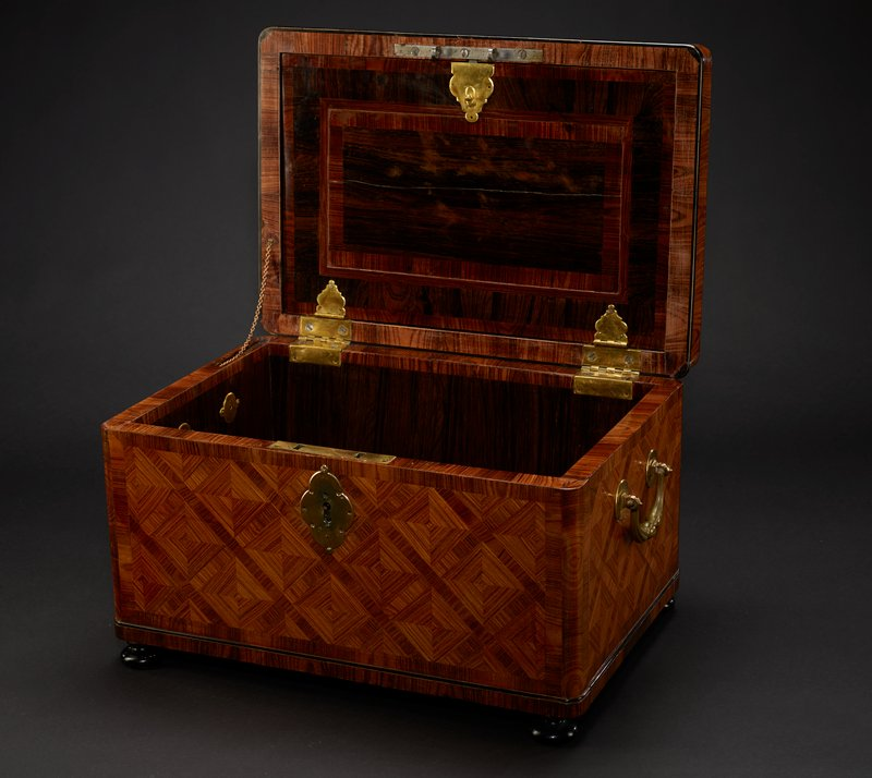wooden box with inlays in diamonds throughout exterior; pair of brass handles on short sides; hinged cover has drop-down inner storage space; various types of wood at interior in rectangular designs on underside of cover and interior bottom; hidden compartment on PL side with drawer at PL bottom with inner four-compartment wooden box with sliding covers and green ribbon at one short side