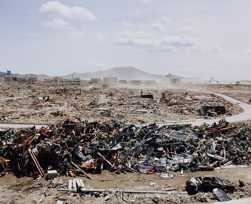 debris/rubble in piles in foreground and beyond road in middle ground; damaged car, LRC; some buildings in background; low mountains