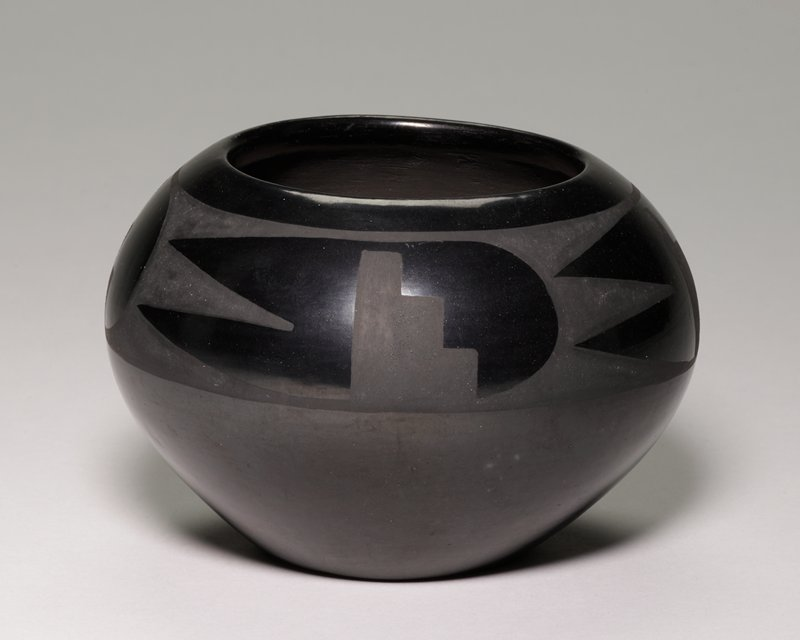 shiny black patina; small flat foot; wide rounded shoulder; wide mouth opening; band around shoulder with repeating geometric pattern with steps, rounded area, and V-shaped zigzag in dull grey/black