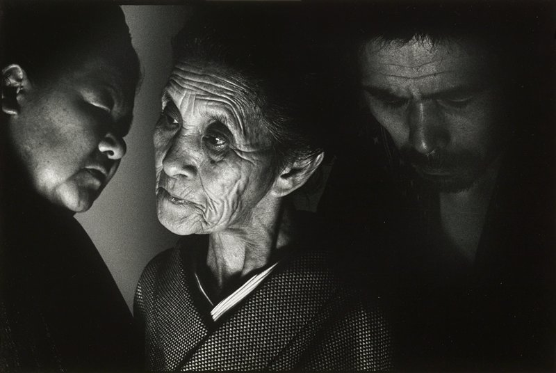 shadowy close-up of three faces with plump woman at left, elderly wrinkled woman at center and man with creased brow at right