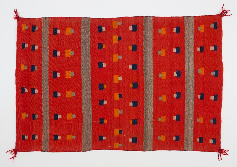 red background with rows of small navy and orange squares with small teal and tan overlapping squares; 4 gray bands; small red tassels at corners; heading band; Velcro header on reverse
