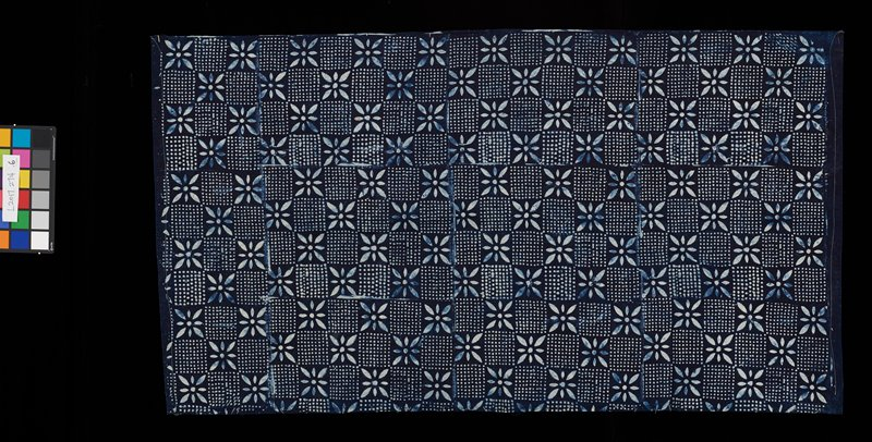 indigo background; alternating pattern of spotted squares, and squares with a flower; has heading band