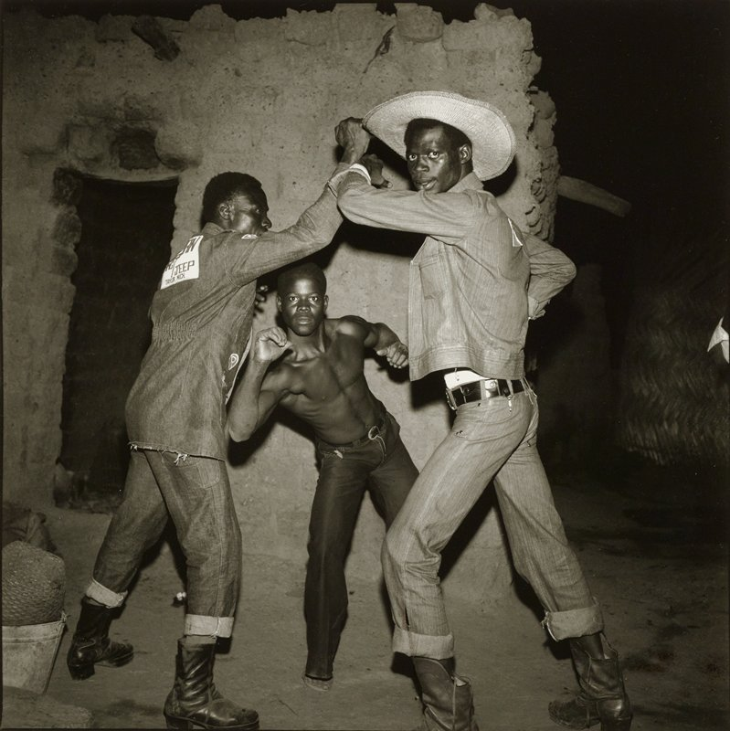 three black men in front of an adobe-like wall at night; two men in front push on each other with their forearms, while shirtless man in back partially crouches and looks beneath other men's arms; man at right wears a cowboy hat; both men in foreground wear denim jackets, rolled-up jeans and boots