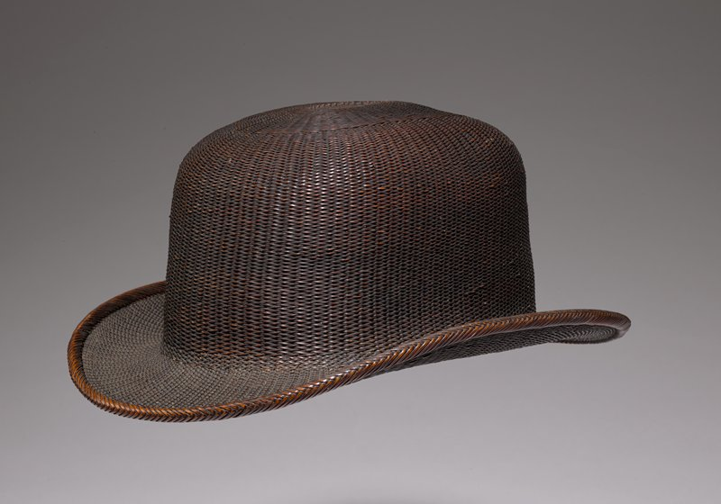 brown rattan woven bowler hat; small loop on back; gold oblong patch with gold brocade on inside at the top; colorful leather embossed band on inner rim
