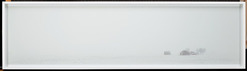 panoramic view of a rural landscape; snowy scene with a misty view of a farm in the LRC; white sky with a field coated in snow; white outer border around all four sides of image