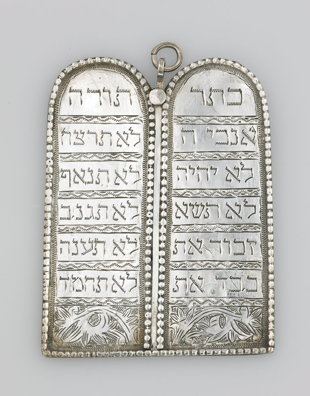 pair of silver tablets attached together at center; fluted edge; incised floral design on bottom of tablets; 6 lines of text on each tablet; one line of text on back