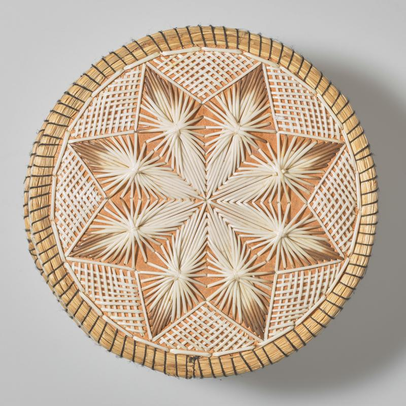 round box with flat top and bottom; top of cover decorated with eight-pointed star with floral starburst inside in white and white fading to brown quills; triangles with grids of quills around edge of top; edges of cover and box decorated with X motifs and grids in white quills; black thread