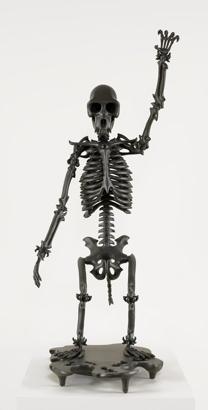 standing monkey skeleton, waving with his PL arm, in black with some additional pointed articulations on bones; attached base with cutouts on front; black