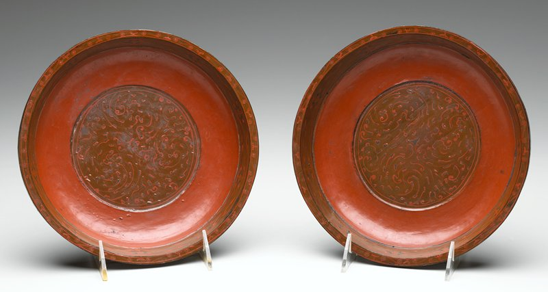 shallow dish with small flaring lip; brown rim with red and black geometric designs; central circular section with brown ground and red organic designs; brown exterior with red and black decoration at edge