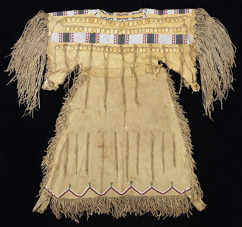 fringe at hem and sides with long fringe around arm openings; sleeveless; rectangular areas of geometric beading (mostly white) on shoulders with iridescent blue and matte beads around neck; 2 rows of bone fragments carved to resemble elk teeth on chest and upper back with one beaded rectangular stripe and another row of bone fragments below; hanging pairs of decorative laces throughout; beading at hem