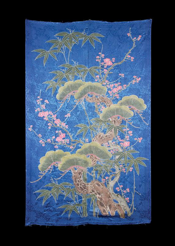 blue silk panel with blue brocade flowers in a repeating pattern in background; branches with pink flowers throughout; tree with thick bark and curving fan-like leaves in bottom R and extends upwards toward top R; green bamboo branches behind larger tree