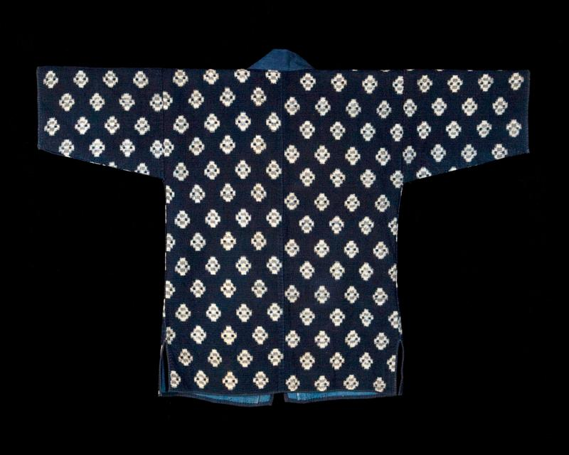 dark indigo coat with repeating pattern of white diamond shapes; blue lining around neckline and opening