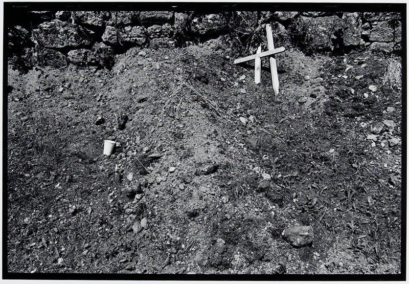 mound of dirt with broken wooden cross