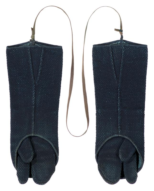 pair of navy blue, tightly knit gloves; three fingered glove (thumb and index finger are individual) inside sleeve covering; covers are connected by olive green cord, knotted to loops on open ends