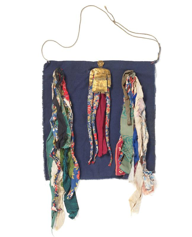 cloth amulet with thin string as strap; blue square piece of cloth, with a small, metal figure in T center; strips of colorful cloth hangs downward from top edge