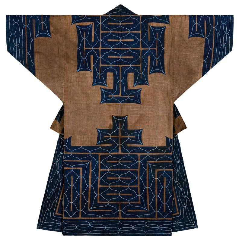 brown plaid robe covered with stepped navy blue applique trim on sleeve cuffs, collar and yoke, center back, and nearly covering bottom section; light blue embroidery over navy applique creates curving lines and points