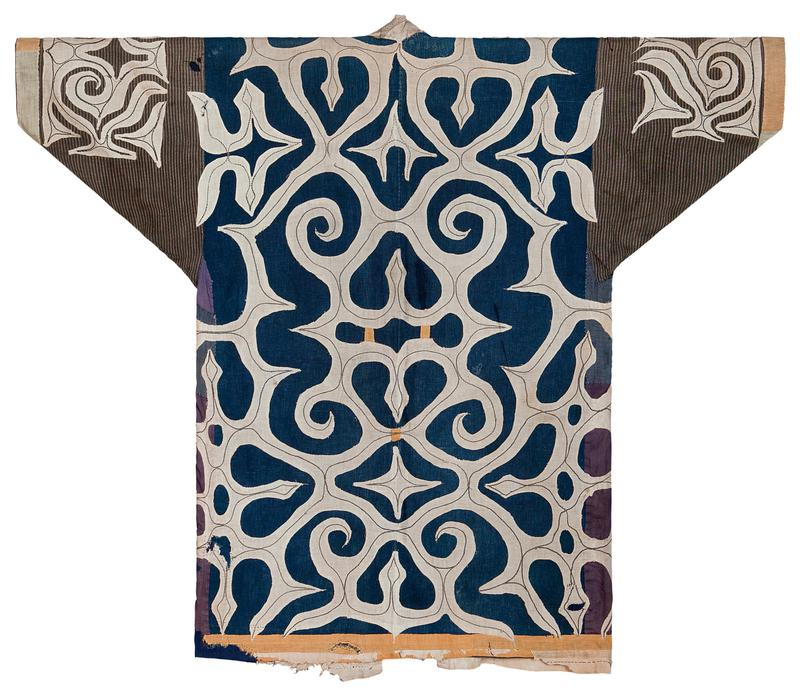 navy coat with wide white applique in organic, swirling pattern; sleeves are contrasting fabric with charcoal background and light stripes; vertical yellow bars near front collar