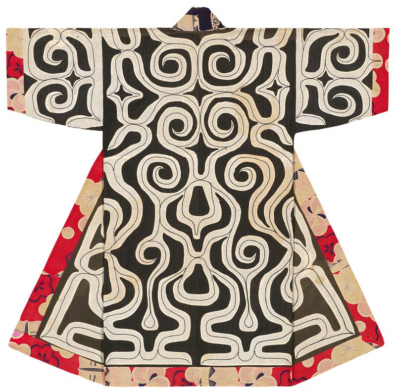 large organic, abstract motif in white applique over navy background; black accent stitching over white applique; floral pattern in reds along hem, cuffs, and inner opening; blue abstract pattern around collar