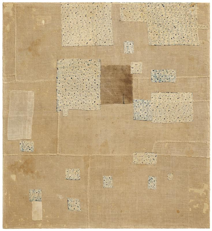 blue and beige patterned fabric squares of various sizes sewn onto a pieced together, tan fabric background; two light beige patches sewn on L side, and one brown patch at C; white stitching on patch edges and as accent
